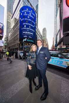 Celebrating the launch of his new book Unshakeable, Tony Robbins poses for a photo with Arianna Huffington in front of the Nasdaq Tower in Times Square