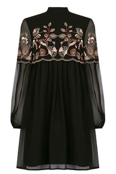 094b2112bd2c5 This embroidered babydoll dress is constructed from a soft woven fabric and  features a high neck