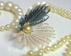 Quilled oyster with pearl. Could do something similar with ribbon