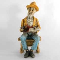 SOLD - Collectible porcelain ceramic figurine of an old man wearing blue pants with a yellow coat and hat sitting on a bench and holding a pipe and book.  The finish is an antiqued matte or bisque. #Collectible #Figurine #OldMan