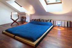 This is a super unique attic bedroom storage idea or even for a loft. Look at how the bed area is pushed out from the wall a little bit. Behind the bed is where all of their books are being stored without a shelf. In this type of room, there really isn't much space for shelving, so they made the best of it by creating that space for their belongings.
