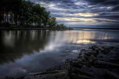 The gathering clouds over the Illinois River and the hope that they contain some much needed rain for the parched earth. The sunlight barely peaks through the clouds as it sets on the far horizon. The calm waters barely make a sound against the rocky shore.
