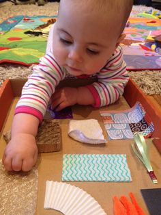 Baby playing on a homemade sensory board. DIY it is so simple and babies find it fun and educational. Good for tummy time too.