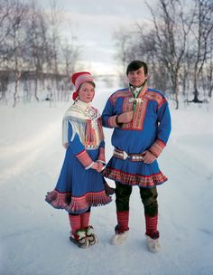 SAMI | Father and daughter dressed for her confirmation. The garb that they wear identifies their hometown as Kautokeino, Norway. The upturned tips of their reindeer-hide boots were designed to hook into skis. [Photograph by Erika Larsen]
