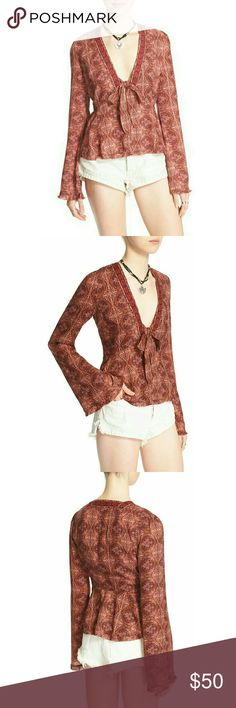 New! Free People V-neck Tie-front Bell Sleeve Top Bold contrast trim and a?drapeyfront tie accent the plunging V-neckline of a?boho-inspired bell-sleeve top patterned with an intricate, kaleidoscopic print. Another Free People, free-spirited look with worn-in vintage appeal.  V-neck with tie closure  Snap buttons at front  Long bell sleeves  100% rayon  Machine washable  Retails for $128 Free People  Tops