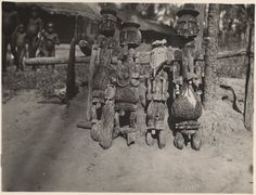 """Nigeria, small group of Ibibio """"ancestral figures"""", made of carved wood. Possibly represent adult males. Leaning against wooden fence [?] outdoors. Single-storey buildings and small group of children in background. Medium: Gelatin silver print."""