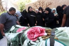 Mourners on Friday stand next to the body of Sondos al-Basha, a Palestinian woman who...