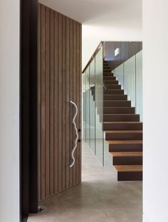 Modern Stairs // Oversized wood pivot door and minimalist stairs at the Bluff House by Inarc Architects