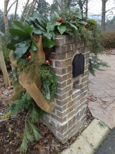 Christmas Mailbox Decoration - Antique Gold Deco Mesh and Red Ornaments decorate this brick mailbox covered in lush Evergreens and Magnolia.