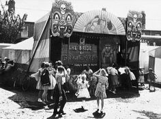 The Midway Bride of Frankenstein featured in this British photograph, one probably from the Fifties, of a tent foldout display painted with skulls, hellish faces and a very prominent topless victim overhead