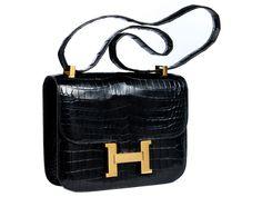 """Ca. 18 x 24 x 5 cm. Schwarze Umhängetasche aus schwarzem Krokoleder mit langem Schulterriemen mit goldfarbenen Beschlägen und großem """"H""""-Klappverschluss...."""