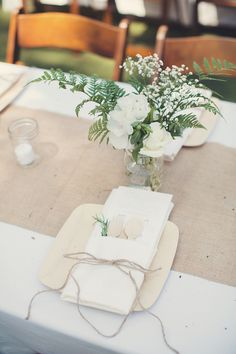 simple centerpieces, ferns+baby's breath+white garden roses on white table clothes with burlap runners, perfect for rectangular tables.