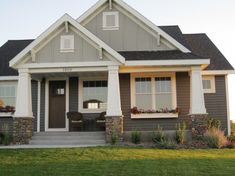 Exterior batt & board with decorative vents, gables, and tapered pillars with stone bases.