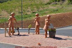 photo du nouveau rond-point à l'entrée du village d' AGUESSAC en AVEYRON - FRANCE Ces sculptures réalisées avec des pot de terre representent des personnages qui travaillent la vigne, celle-ci est une des cultures de cette région. Le rond point est actuellement...