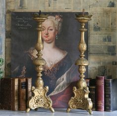 Gold altar candlesticks, old books and antique painting against newspaper background.