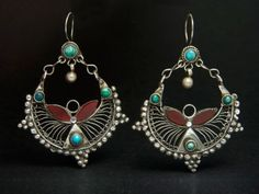 Old silver Kutchi earrings,  A superb set of old silver Kuchi earrings from Afghanistan. The design is vey original. The combination of different techniques in their making is very successful and appealing. They are further ornated with small cabochons of turquoise and deep red glass. Certainly, eye-catchers.