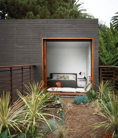 A guest bedroom, with furniture from Room & Board, overlooks the bridge above the dining courtyard. The home's landscape architecture...
