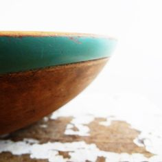A rare antique wood bowl with a blue-green painted rim. The bowl originally dates to sometime around the mid-1800s. The paint was likely added in about the 1930s, and someone varnished over the paint in the 60s or 70s to prevent wear.