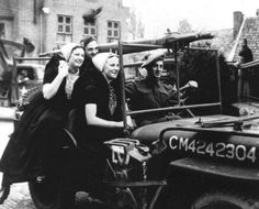 Two local women from Zeeland hitch a ride on a jeep with allied soldiers during the liberation parade (May 5th, 1945)