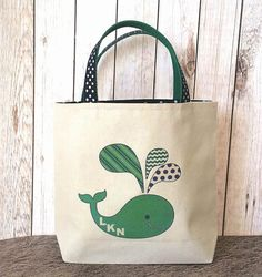 Handmade canvas tote lined with navy polka dot and navy polka dot ribbon and green webbing handles.Original Artwork adorns the front with a Whale logo with your choice of initials,name or favorite beach in place of LKN. The design is heat pressed with a vintage look. Made for your little one to tote all their things to the beach,pool or just to the sandbox...plenty of room for their little towel and a shovel or two. Made of a durable canvas to withstand lots of play.  Childs name, Vacation…