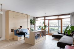 The space-saving furniture is made up of several modules. The main pieces are a ceiling-height storage unit, which integrates the fold-down bed, and a library-style bookshelf.