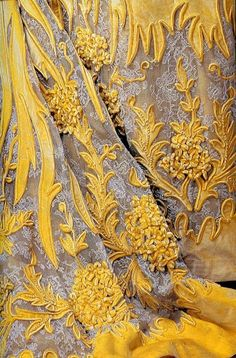 Detail of Russian gown (circa 1896) with appliqued golden yellow velvet against embroidered lace kerchief.