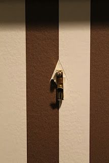 When hanging anything on top of wallpaper, I recommend you don't put the the nail through the wallpaper. You will create a small whole in the wallcovering that can not be fixed or hidden in the event you want to move the artwork or frame. Instead, using a utility knife, cut a small upside down V, pull the wallcovering back gently and then put the nail through the drywall.