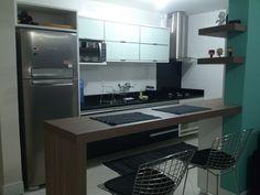 Foto de cozinha feita para um casal de Gravataí-RS. Amadeirado, vidro branco e granito são gabriel.