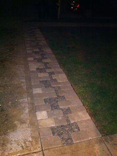 Walk path next to the driveway. Pavers and black stone.