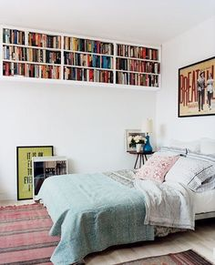 White Bedroom with Bookshelves Hung High on Wall and Woven Rug. For even more storage, consider hanging shelves up high that run the length of the room. You won't loose any floor real estate at all, and you'll gain a lot of storage space.