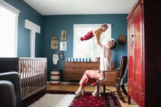 Beautiful inspiring boys nursery. Blue walls, oriental rug, pops of white