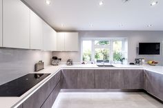 This beautiful kitchen in Bushey, comprises of Grey Concrete effect base units and White High Gloss tall and wall units. This modern handle-less design is completed with a…