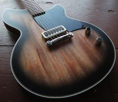 This single pickup junior style build has beautiful diagonal checker purfling with white binding, a McNelly P90 size Cornucopia humbucker and an ABM Germany featherweight wraparound bridge. All other specs listed below. This is simply a fantastically solid stripped down guitar with just the rig...