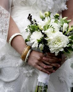 Taryn wears Mark Davis bangles and carries a bouquet made by Amy Kate Designs of dahlias, Veronica, lysmachia, privet berries, and eustoma. White ostrich feathers and a collection of herbs and foliage finish it off.
