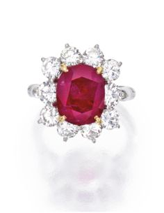 PLATINUM, RUBY AND DIAMOND RING  Estimate: 160,000 - 200,000 USD   The cushion-cut ruby weighing 6.53 carats, framed by ten round diamonds weighing approximately 2.30 carats, size 5¾.