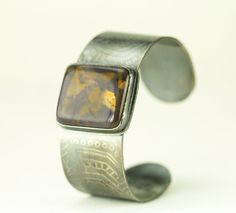 Beautiful sterling Purple Flame Jasper cuff bracelet with a deeply etched etched flower pattern solid sterling bracelet.Featuring an incredible highly polished unique stone, this Purple Jasper Cuff has an etched lotus pattern on a 1 inch wide sterling bracelet cuff. This pattern statement cuff features a moderate size rectangular purple flame jasper cabochon set in fine silver and the pattern oxidized to show detail. This is a solid heavy bracelet yet remains flexible enough to adjust…
