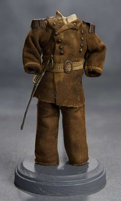 "Of dark taupe linen, the two-piece ensemble features a tunic with rows of decorative buttons, metal epaulets on the collar, braid trim, belt, and with matching pants. With soft metal sword. For 7""-8"" doll. 2 1/2' shoulder width. Circa 1890."