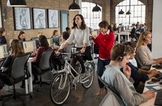 Anne Hathaway sports a chunky knit and black skirt whilst riding her retro bike around the office in The Intern