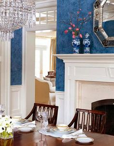blue and white dining room with a crystal chandelier, dark wood, mercury glass/silver and gold accents