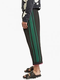 The Haider Ackermann Dropped-Crotch Trousers for SS17, seen here in black and green. These trousers from Haider Ackermann are crafted from a premium linen-blend and cut to offer a relaxed fit. A unique dropped-crotch style, they are finished with stripes to the sides and a turned-up hem.