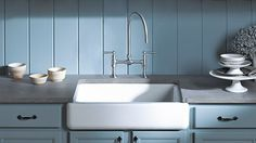 The contrast from the gray countertops and blue cabinets and backsplash to the white Kohler apron front sink is very calming to the eye.