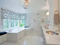 This bathroom is a luxurious space filled with gray tile. A fun fabric shade not only loosely mimics the floor tile pattern but frames out the tub area, making it feel as if it's tucked in a cozy corner.