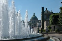 """Beautiful fountain in the harbour of the Amalienborg Palace Square. The Marble Church (Round Dome) in the background. Copenhagen, Denmark. Princess """"Star"""" Ship."""