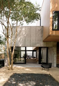 Concrete Box House by Robertson Design - Houston, Texas Couple Builds Modern Concrete House Sliding doors from Western Window Systems connect the living room and the deck, which is made of pressure-treated pine planks surrounding a black gravel pit. House Architecture Styles, Residential Architecture, Interior Architecture, Concrete Architecture, Architecture Unique, Modern Japanese Architecture, Concrete Houses, Concrete Wood, Concrete Design
