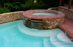 Swimming Pool and Raised Spa with stone wall and stamped concrete pool deck in Greensboro, NC.