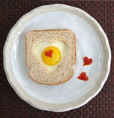 Heart shaped eggs for breakfast with red hearts made with ketchup or sriracha. Cute Valentine's Day idea!