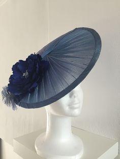 Tocado base sinamay seda con flor peonia de seda y pluma azul. Sujeción con diadema. PVP: 40€