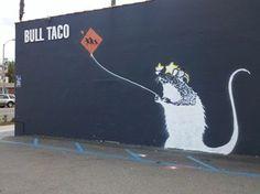 Banksy tag on Bull Taco shop's exterior.