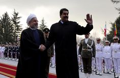 Iranian President Hassan Rouhani (left) shakes hands with Venezuelan President Nicolas Maduro after reviewing the honor guard at the Saadabad Palace in Tehran on January 10, 2015 (AFP Photo/Atta Kenare)