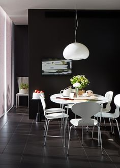 Flos Black and White pendant light, painting by Andrew Brown, Fritz Hansen table and Ant chairs, Tom Dixon small table.